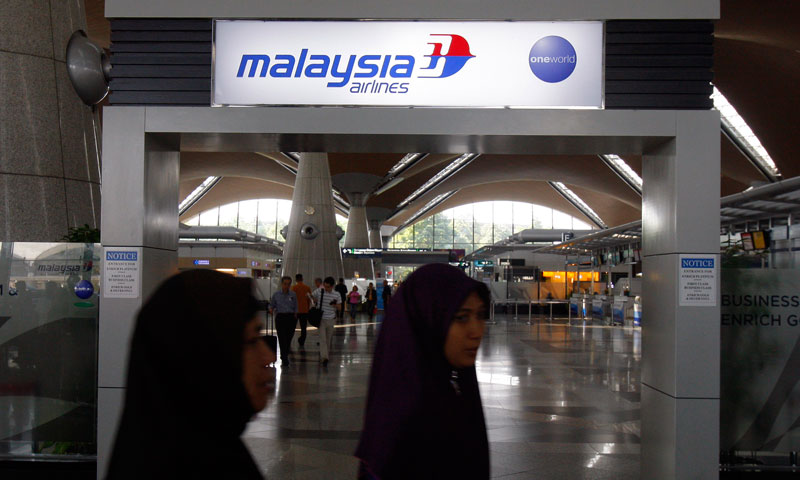 Passengers walk past a signboard of Malaysia Airlines at Kuala Lumpur International Airport in Sepang, outside Kuala Lumpur, Malaysia, Saturday, March 8, 2014. — Photo by AP