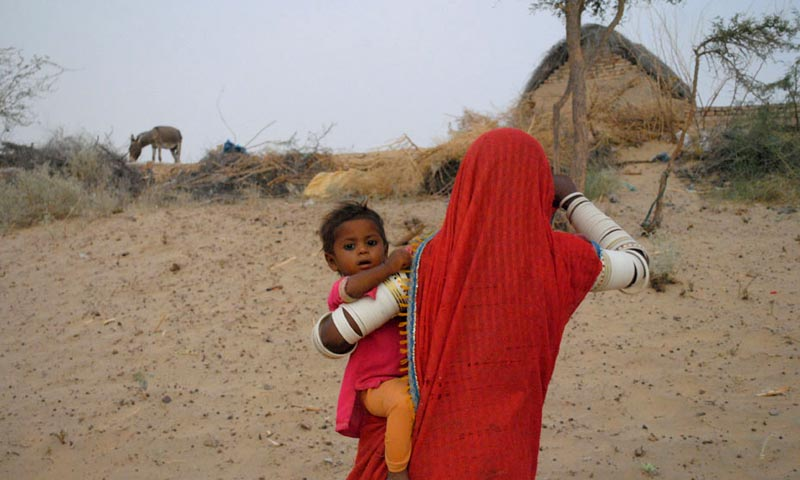 Image shows a native woman of Tharparkar with her child.— Photo by Hussain Afzal
