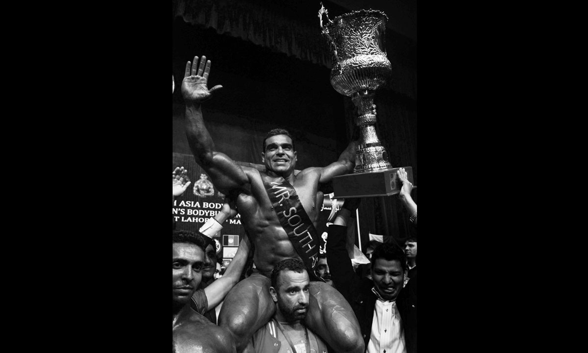 Pakistani bodybuilder Shoukat Shahzad celebrateswith his trophy during the 10th South Asian Men's bodybuilding championship. – Photo by AFP