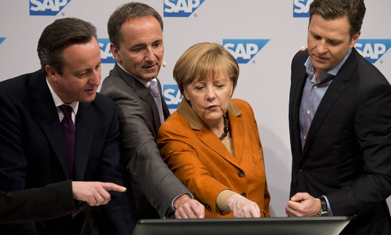 Britain's Prime Minister David Cameron, SAP co-CEO Jim Hageman Snabe, German Chancellor Angela Merkel and manager of the German football team Oliver Bierhoff watch how real-time data analysis of a football game can improve team performance during a presentation at the SAP stand of the 2014 CeBIT computer technology trade fair on March 10, 2014 in Hanover, central Germany. — AFP Photo