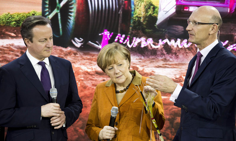 Britain's Prime Minister David Cameron looks on as German Chancellor Angela Merkel touches phone cabling presented by Deutsche Telekom CEO Timotheus Hoettges during a presentation on high capacity fiber-optic cables at the Deutsche Telekom stand of the 2014 CeBIT computer technology trade fair on March 10, 2014 in Hanover, central Germany.— AFP Photo