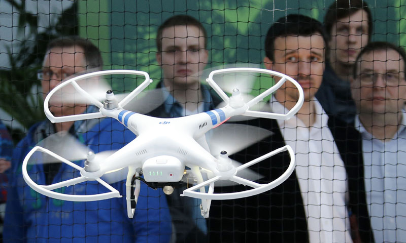 """Visitors watch a """"Phantom 2"""" drone by dji company at the CeBIT trade fair in Hanover, March 10, 2014. — Reuters Photo"""
