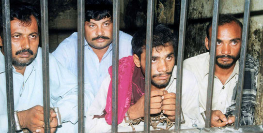 Four men, charged in connection with the gang-rape of Mukhtar Mai, sit inside a police lockup at Ali Pur near Multan in this July 16, 2002 file photograph. Mai, a victim of a village council-sanctioned gang-rape who became a symbol of the country's oppressed women, said on April 21, 2011 her life was in danger after the Supreme Court acquitted 14 men accused of the crime. The men are (from L to R) Ramzan Pachar, Faiz Bukhsh Mastoi, Abdul Khaliq and Allah Ditta Mastoi. The death penalty for Abdul Khaliq was commuted