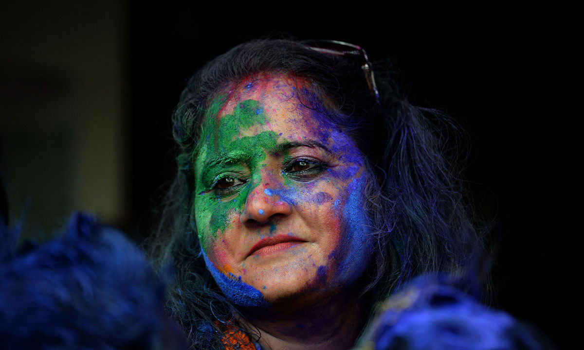 A Pakistani Hindu covered with coloured powder looks on during celebrations for the Holi festival in Lahore, March 16, 2014. — Photo by AFP
