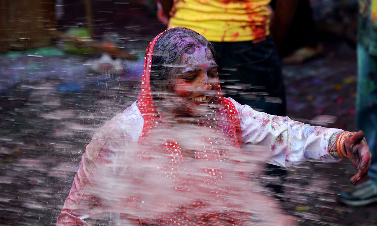 A Pakistani Hindu covered with coloured powder is sprayed with coloured water during celebrations for the Holi festival in Lahore, March 16, 2014.  — Photo by AFP