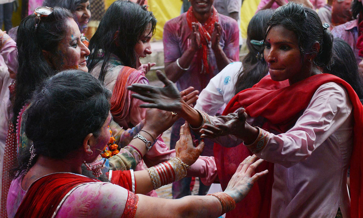 Pakistani Hindus covered with coloured powder greet each other as they take part in celebrations for the Holi festival in Lahore, March 16, 2014. — Photo by AFP