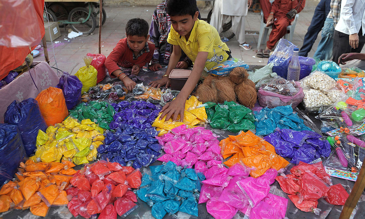 """Young Pakistani street vendors sell coloured powder or """"gulal"""" on the eve of the Hindu festival of Holi in Karachi, March 15, 2014. — Photo by AFP"""