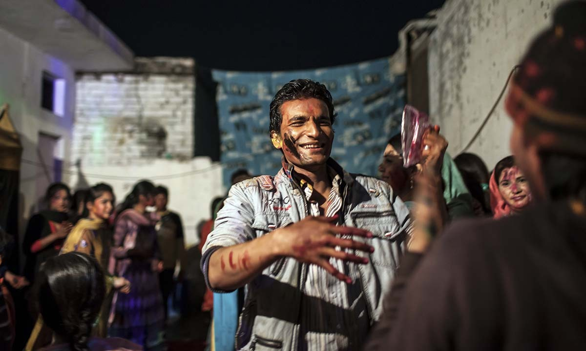 Young men join the festivity of Holi and throw color at each other.   — Photo by Sara Farid