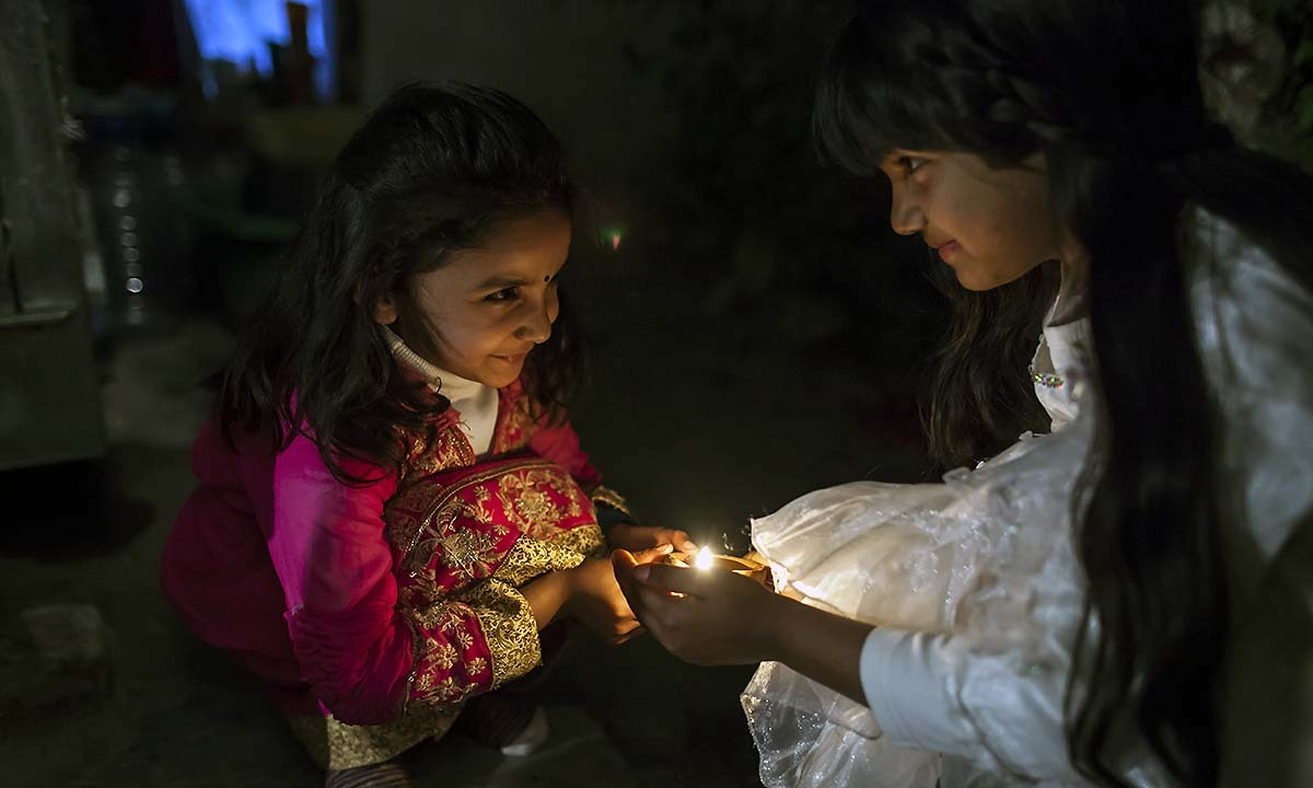 Two yound girls joyfully place an oil lamp outside the temple as part of the Holi celebrations in Rawalpindi, Pakistan.  — Photo by Sara Farid