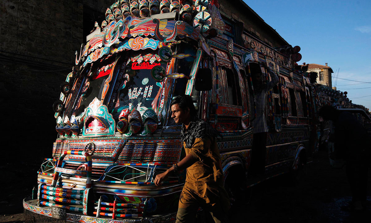 A man walks past a decorated bus parked along a street near to the terminus in Karachi, March 20, 2014.
