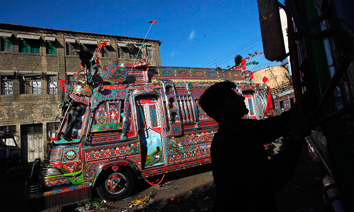 A man is silhouetted against a decorated bus parked along a street near to the terminus in Karachi, March 20, 2014.