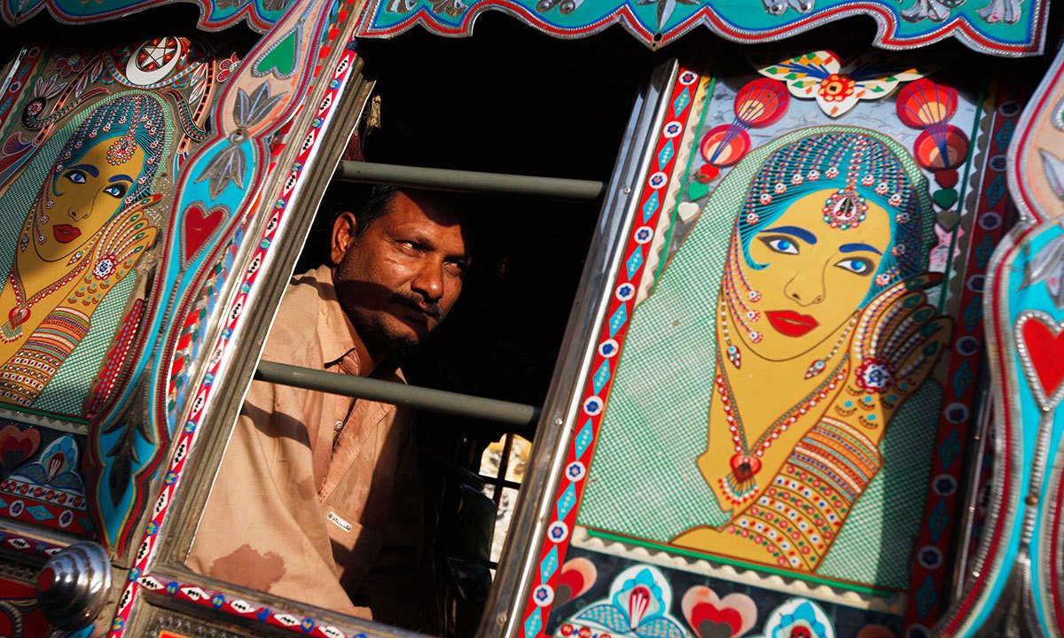 A passenger sits in a decorated bus parked along a street near to the terminus in Karachi, March 19, 2014.