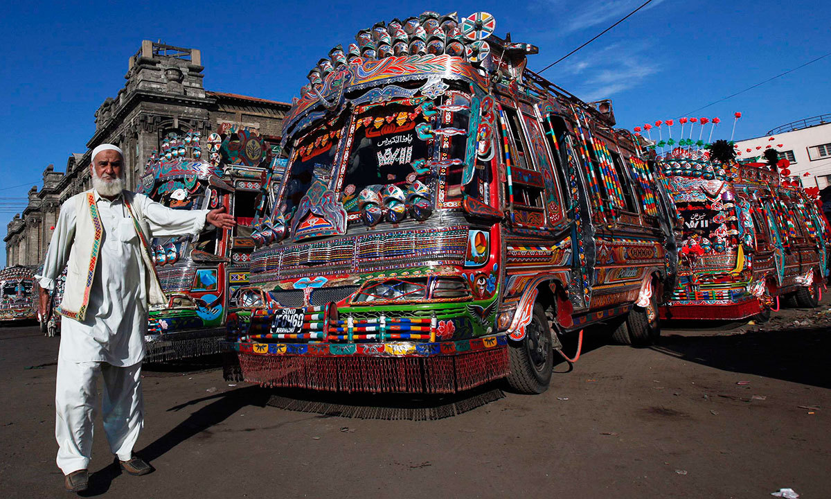 A man gestures as he walks past decorated buses parked along a street near the terminus in Karachi, March 20, 2014.