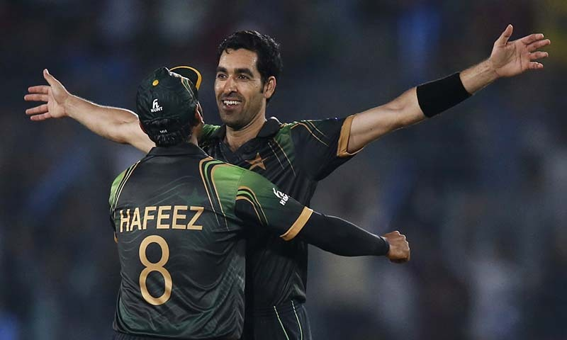 Pakistan's captain Mohammad Hafeez, left, hugs teammate Umar Gul to celebrate the dismissal of Australia's batsman Brad Hodge during their ICC Twenty20 Cricket World Cup match in Dhaka, Bangladesh, Sunday, March 23, 2014. — Photo by AP