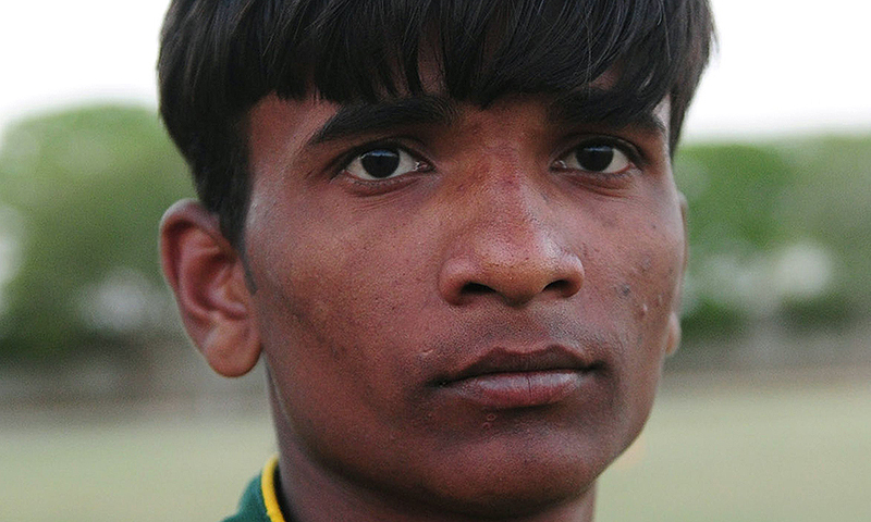 This photograph taken on March 17, 2014, shows Pakistani street child Mohammad Salman posing during a football training camp in Karachi. -Photo by AFP