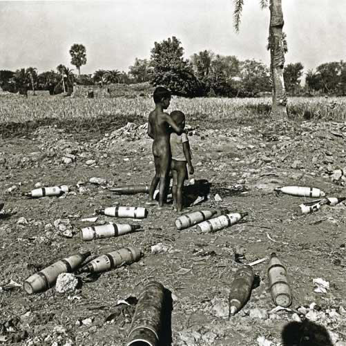 Two peasant children stand amidst unexploded bombs in a village in former East Pakistan during the 1971 Pakistan-India war.