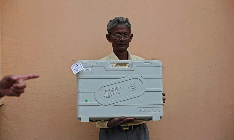 A polling officer holds an Electronic Voting Machine (EVM) as he poses for a picture at a distribution centre ahead of general elections in Jorhat district, in the northeastern Indian state of Assam. —Photo by Reuters