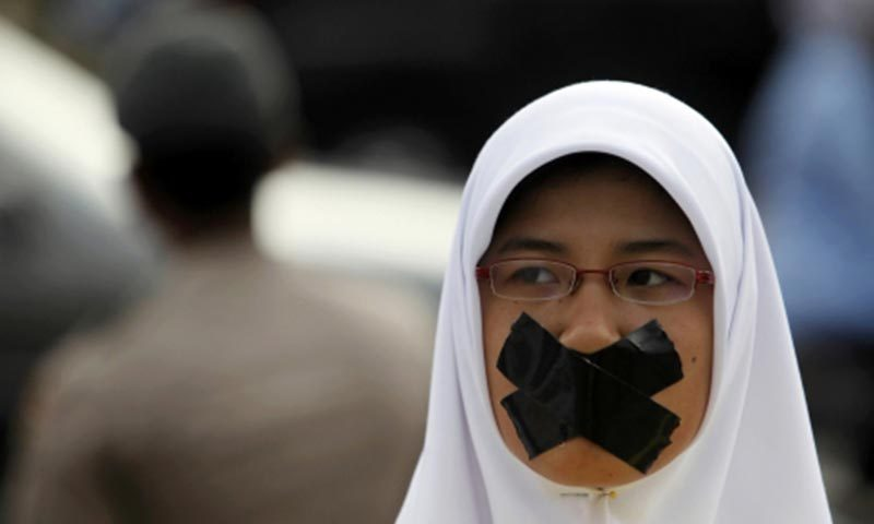 Photo of a student covering her mouth with tape during an Anti-Corruption Day rally in Jakarta. — Photo by Reuters