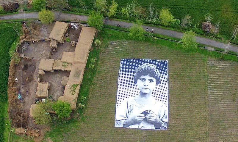 """In this undated handout photograph from the """"Inside Out Project"""", a poster bearing the image of a Pakistani girl whose parents, lawyers say, were killed in a drone strike, lies in a field at an undisclosed location in the northwestern Khyber-Pakhtunkhwa province. -AFP Photo"""