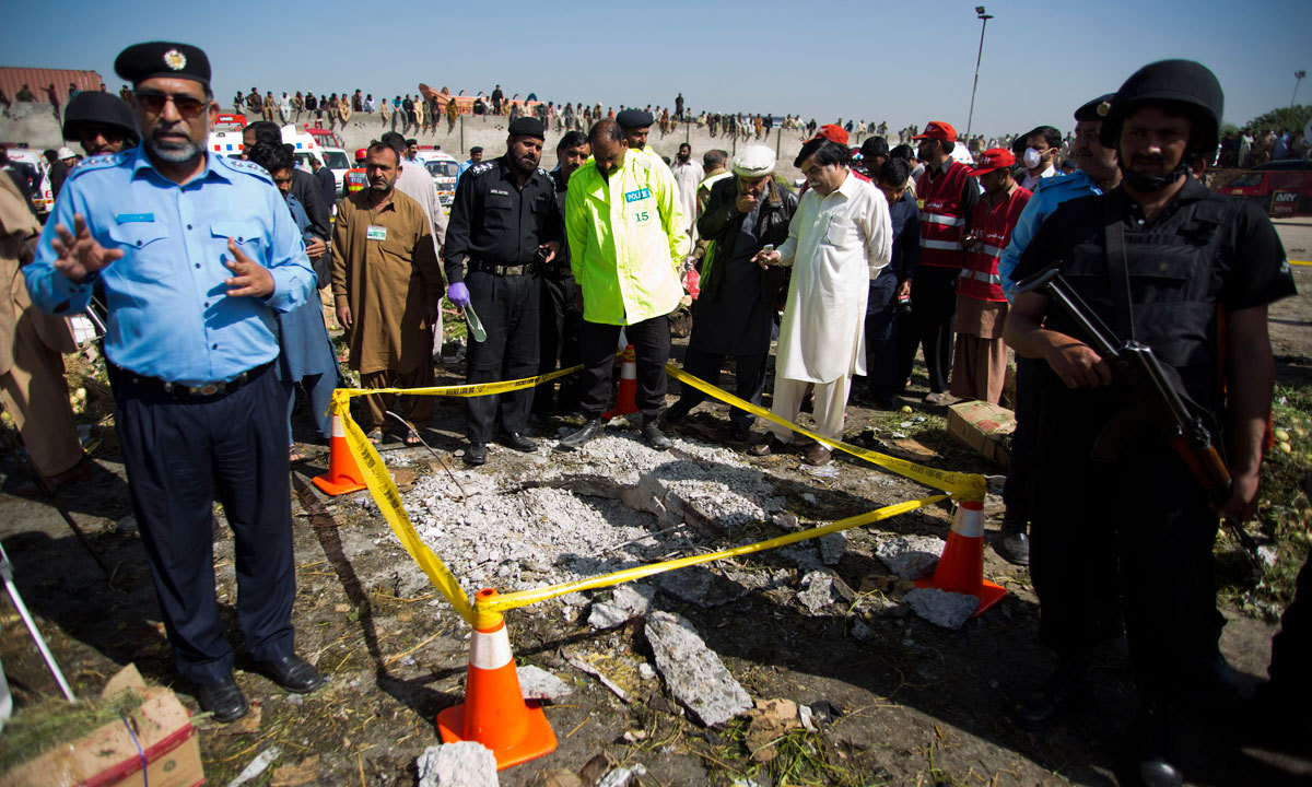 Pakistani investigators gather around a crater following an explosion in Islamabad, Pakistan, Wednesday. – Photo by AP
