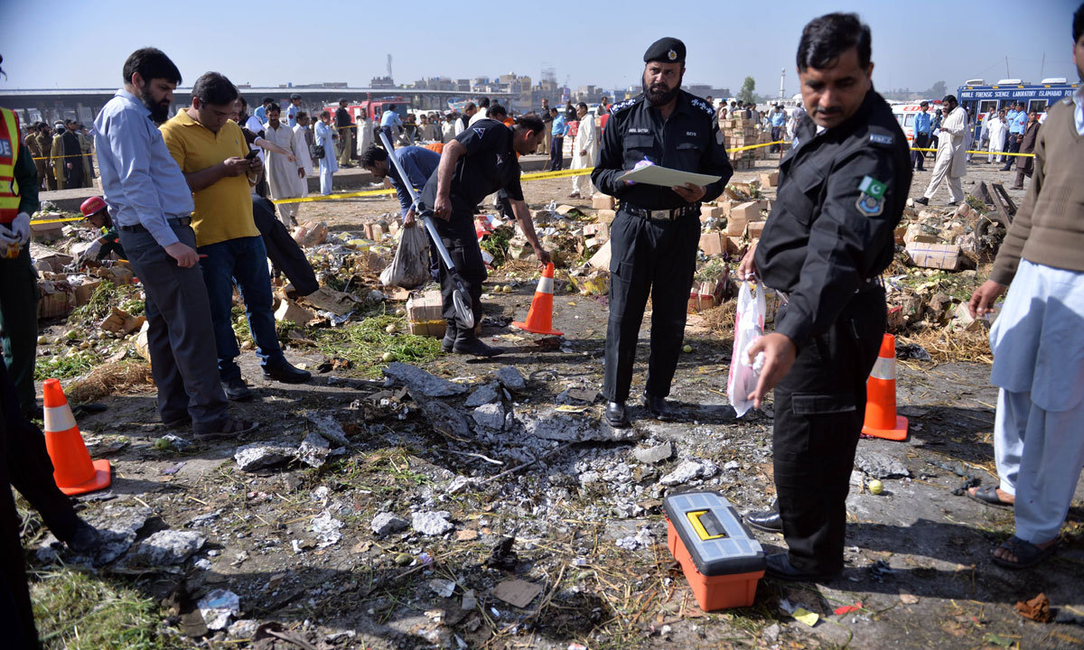 Pakistani security officials inspect the site of a bomb explosion in a fruit and vegetable market in Islamabad. – Photo by AFP