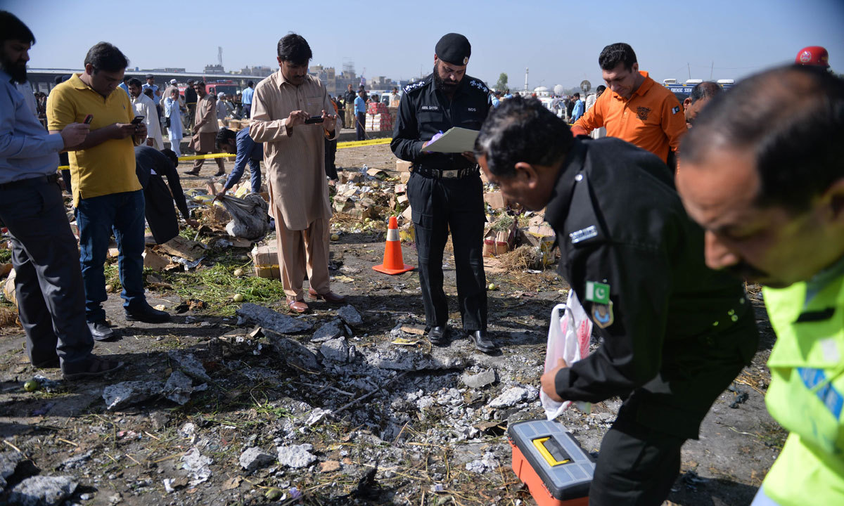 Pakistani security officials inspect the site of a bomb explosion in a fruit and vegetable market. – Photo by AFP