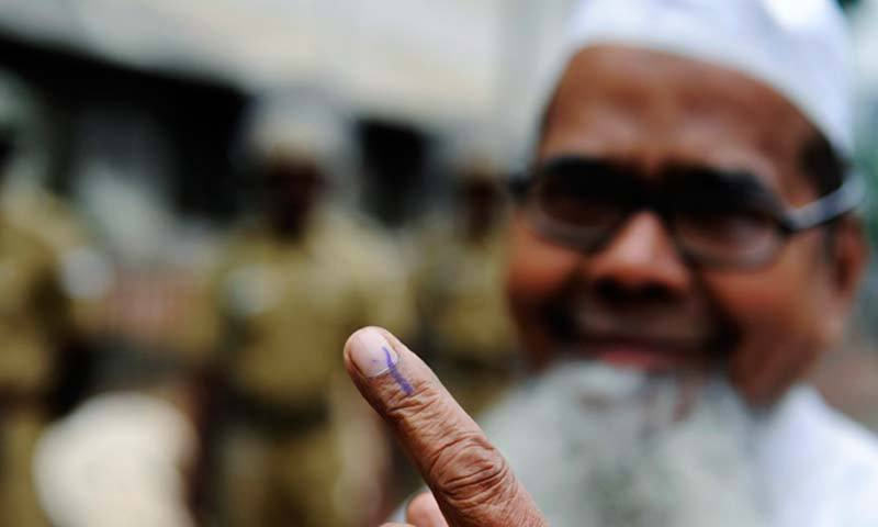 An Indian Muslim shows his inked finger as he casts his vote at a local polling station. — Photo by AFP