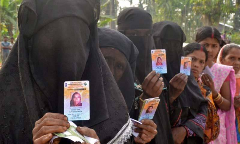 Indian Muslim voters pose with identification as they wait in line to vote outside a polling station. — Photo by AFP