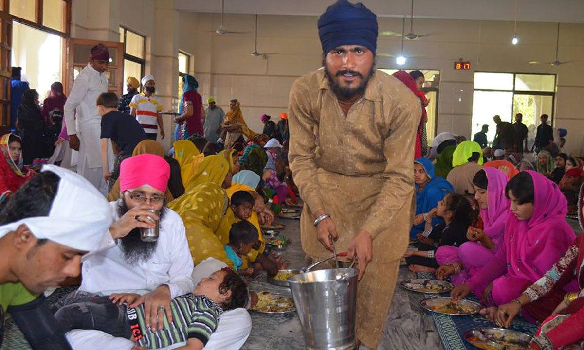 Sikh pilgrims are eating 'langer'.