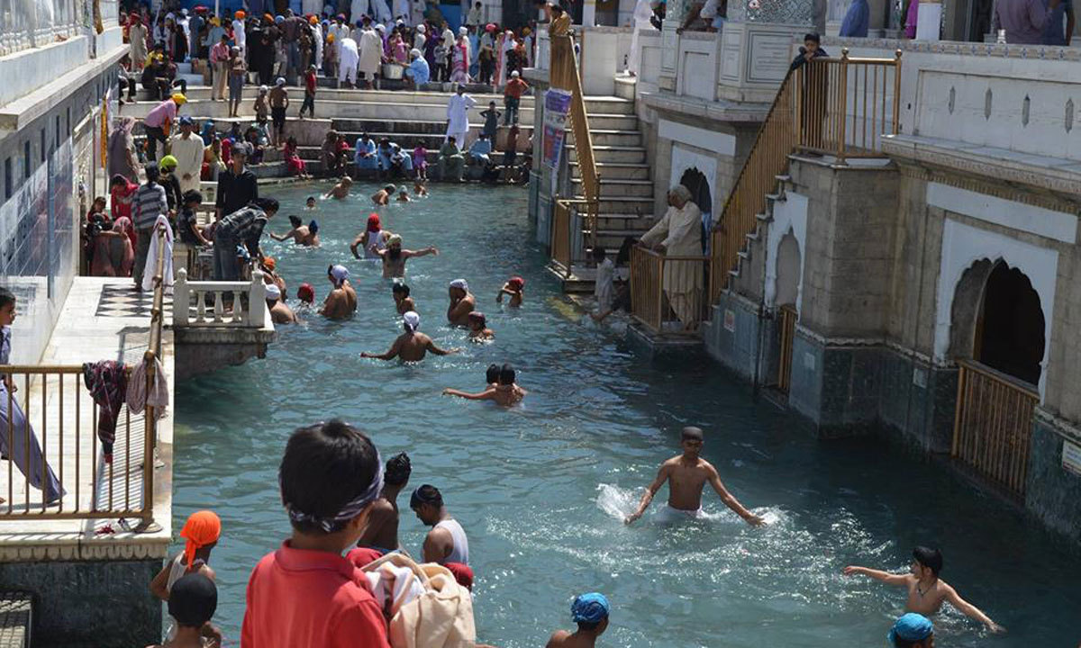 Sikh pilgrims are taking bath in the holy water at Punja Sahib.