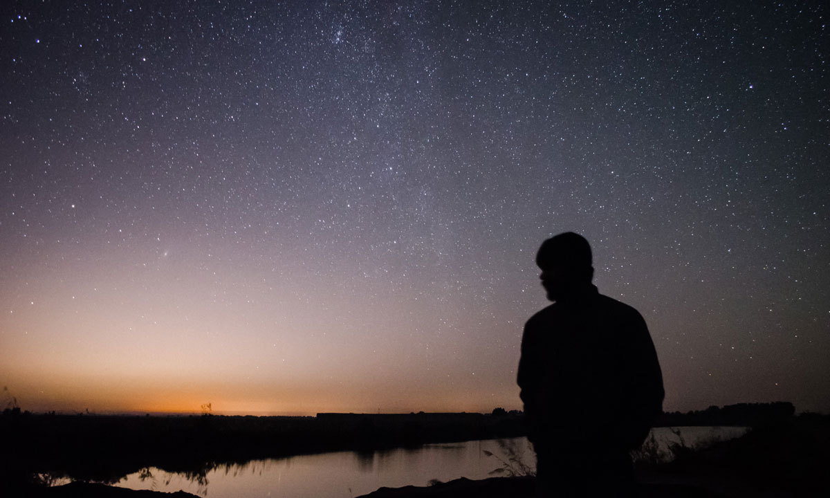 A participant poses against a starry backdrop showing the Andromeda Galaxy (Left) and the subtle, dim Milky Way (Center). Both galaxies are on a collision course over the next few billion years. – Photo by Ramiz Qureshi