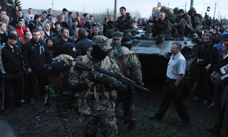 ARMED pro-Russia activists block a column of Ukrainian armoured personnel carriers in the eastern city of Kramatorsk on Wednesday. The Ukrainian military personnel sitting on the APCs are surrounded by local people.—AFP