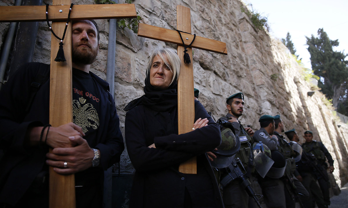 Christian Arab worshipers hold wooden crosses during the Good Friday procession along the Via Dolorosa (Way of Suffering) on April 18, 2014 in Jerusalem's Old City. Thousands of Christian pilgrims take part in processions along the route where according to tradition Jesus Christ carried the cross during his last days. — Photo by AFP.