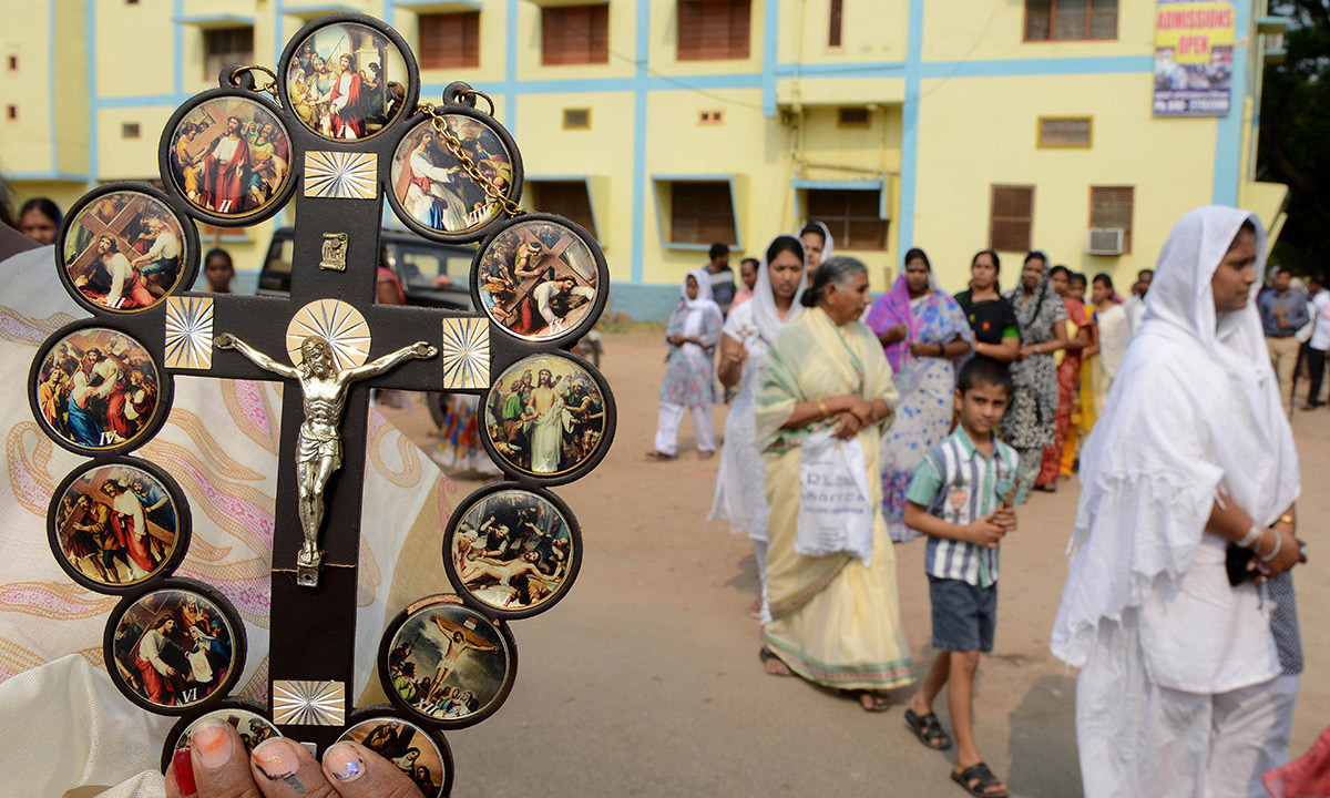 An Indian Catholic worshipper holds up a cross during a procession in remembrance of the crucifixtion of Jesus Christ during a 'passion play' tableau at The Mount Caramel Church in Hyderabad on April 18, 2014. Passion plays, a dramatic presentation depicting the suffering and death of Jesus Christ, are an integral part of Good Friday celebrations for Catholics. — Photo by AFP.