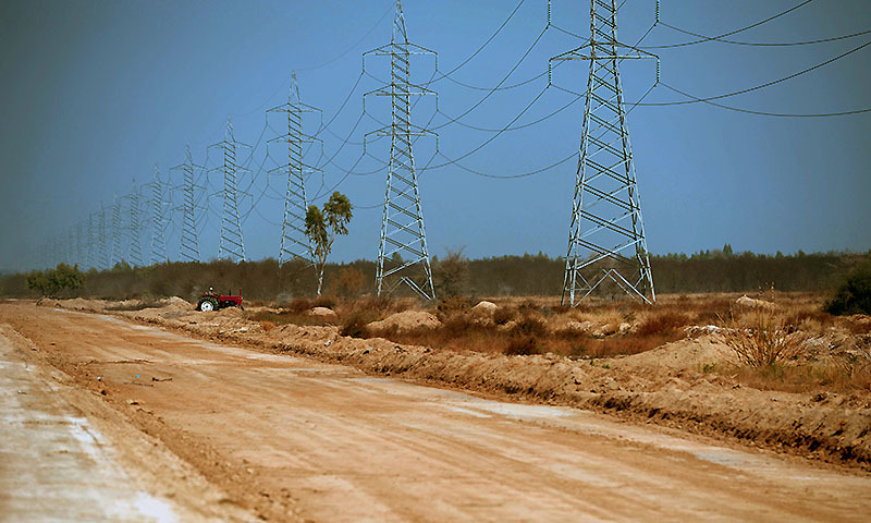 This photograph taken on February 17, 2014 shows a Pakistani villager riding a tractor under high voltage lines at the proposed site of the solar energy park at Badaiwani Wala village in Bahawalpur district of Punjab province.  — Photo by AFP