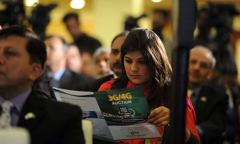A woman reads a brochure of 3G and 4G of next-generation telecommunications during an online auction in Islamabad. -AFP Photo