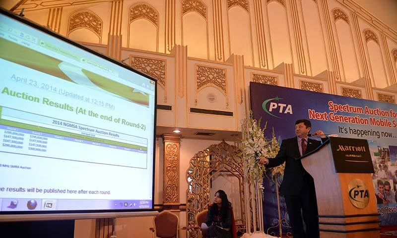Chairman of Pakistan Telecommunication Authority (PTA) Ismail Shah (R) presents an online 3G and 4G licence auction of next-generation telecommunications in Islamabad. -AFP Photo