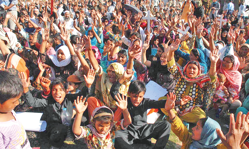 Residents of a katchi abadi raise slogans during a protest outside the National Press Club in Islamabad on Wednesday.—Online