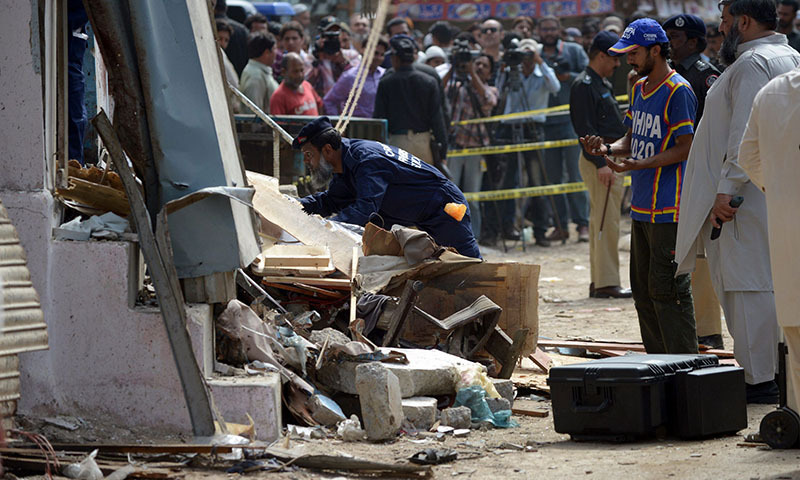 Security personnel inspect the site of a bomb attack in Karachi on April 24, 2014. — Photo by AFP