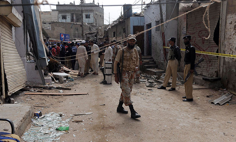 Security personnel inspect the site of a bomb attack in Karachi on April 24, 2014.— Photo by AFP