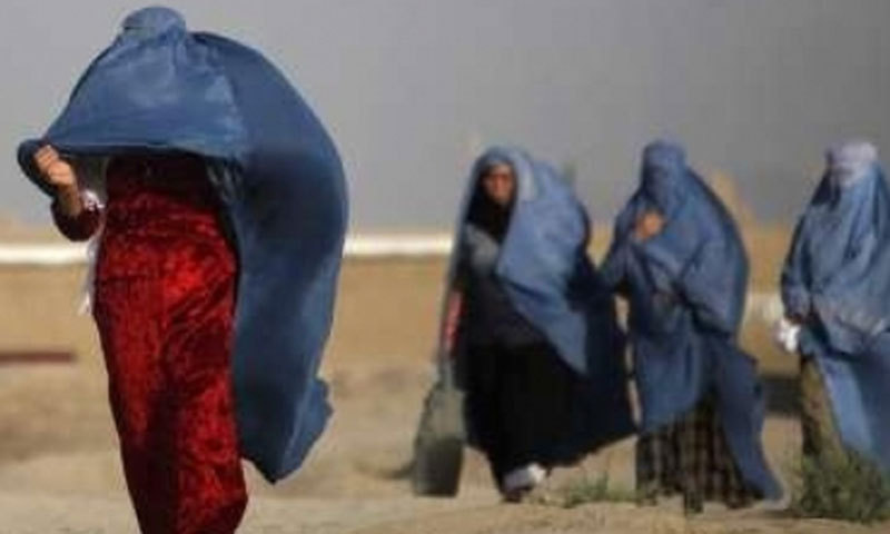 A group of women fighting to hold their  Afghan-influenced blue burqa in place despite the strong wind. File Photo