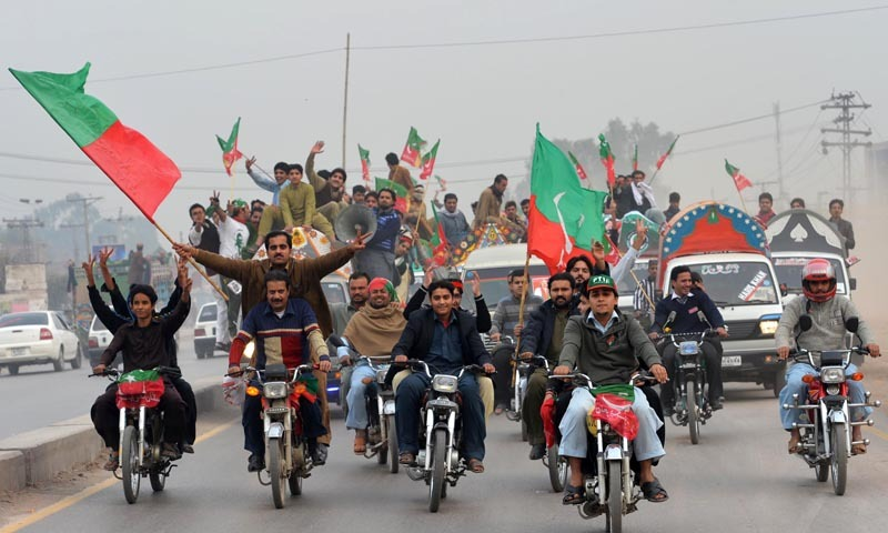 Activists of Pakistan Tehrik-i-Insaaf (PTI) arrive to attend a protest rally in Peshawar. — Photo by AFP/Dawn File
