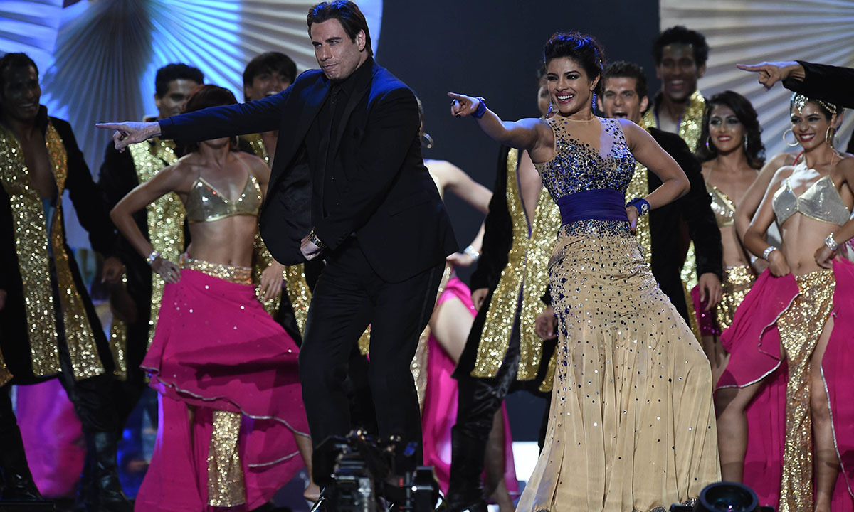 Bollywood actress Priyanka Chopra and US actor John Travota  dance on stage at the Raymond James Stadium on the fourth and final day of the 15th International Indian Film Academy (IIFA) Awards in Tampa, Florida, April 26, 2014. — Photo by AFP