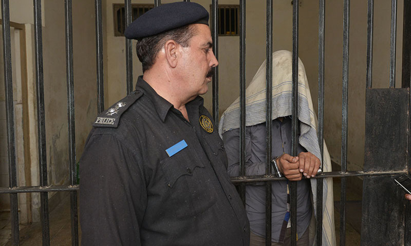 A police officer presents the man arrested on charges of killing homosexual men, at a police station in Lahore on April 27, 2014. — Photo by AFP