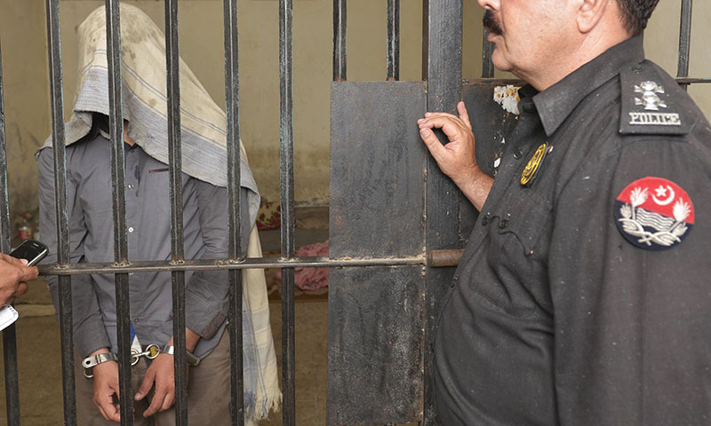 A police officer presents a man arrested on charges of killing homosexual men, at a police station in Lahore on April 27, 2014. — Photo by AFP