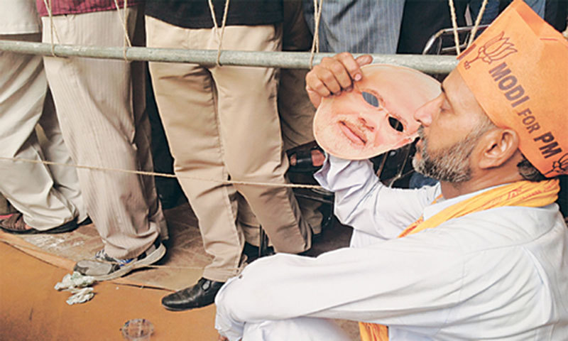 A supporter of the BJP uses a mask of Narendra Modi as fan at an election rally.