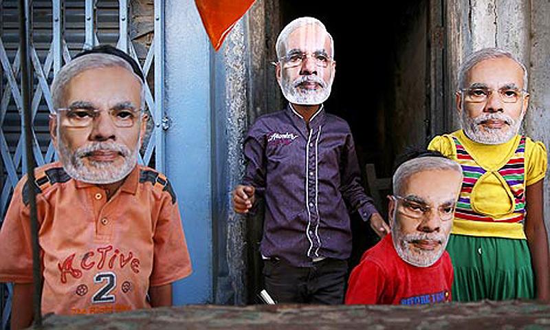 Children play wearing masks of BJP prime ministerial candidate Narendra Modi in Varanasi. -Photo by AP