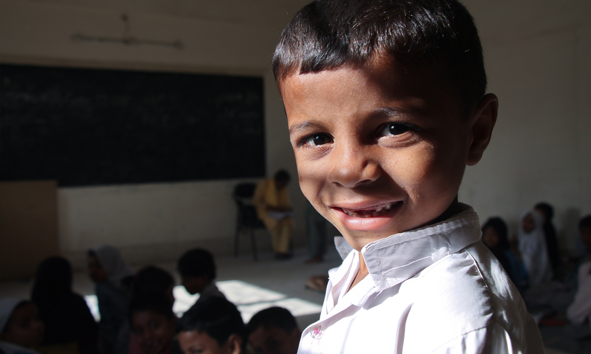 A boys smiles into the camera.