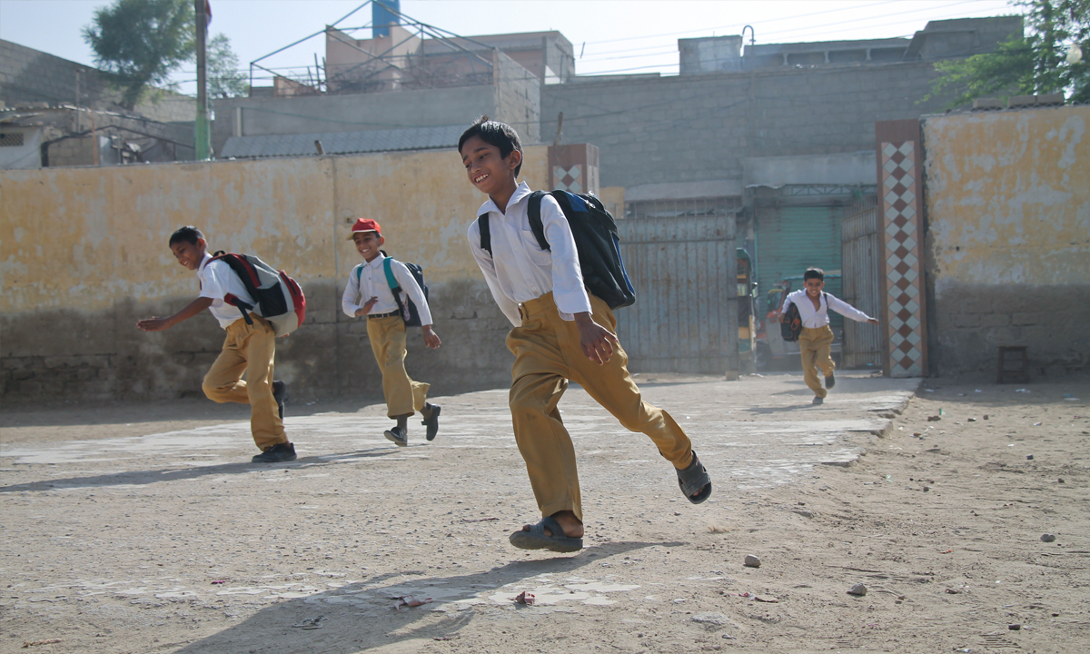Boys run inside the school building, early in the morning.