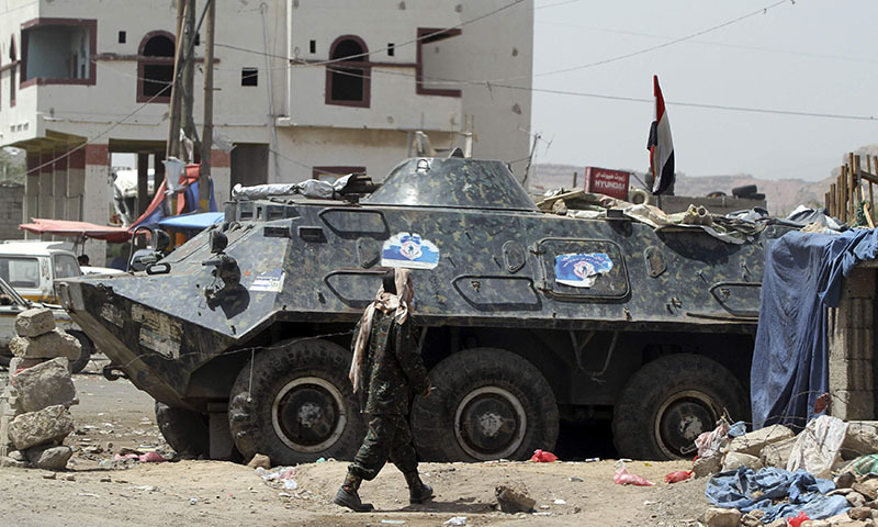 A soldier walks near an armoured military vehicle at a checkpoint  to the city of Sanaa, May 3, 2014.  —Photo by Reuters